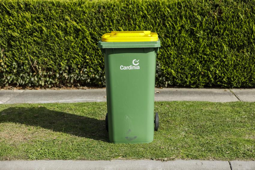 Recycling bin with yellow lid on kerb